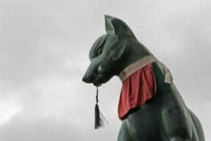 Japanese fox Kitsune statue with red decoration - yodarekake