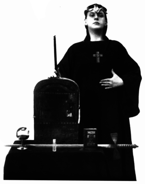Aleister Crowley posing as Magus with the Stelae of revelation and magical weapons: wand, chalice, sword and the Book of the Law – the Liber Al Vel Legis