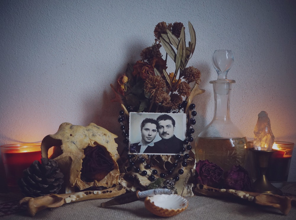 Shrine / altar to rember the ancestors: skull, photo of deceased family, flowers, seashell for offerings, spirits and candles.