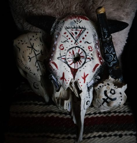Bone magick: a bull skull with magical symbols and sigills on carpet for ritual use.