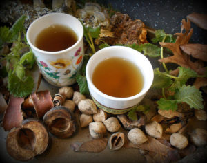 Brewed nettle tea in cups. Beautifully decorated with nettle leaves and wood.