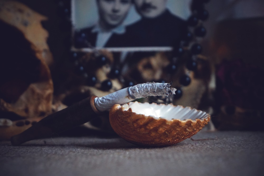 Offering on witches altar: burning cigarette in seashell