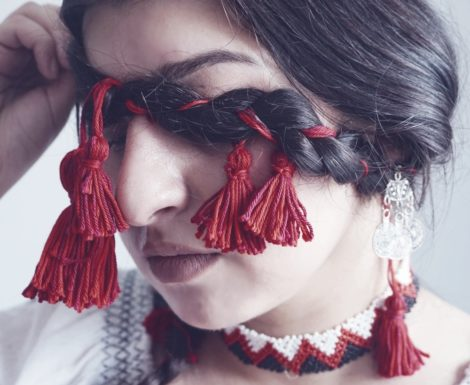 Romanian braided plaits - pigtail - with red cord. Macro on Romanian woman with national costume and traditional Romanian necklace.